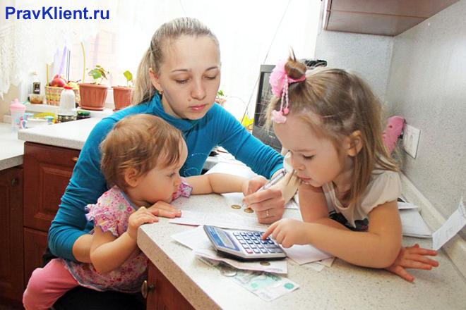 Девушка сидит с двумя дочками на кухне и считывает деньги