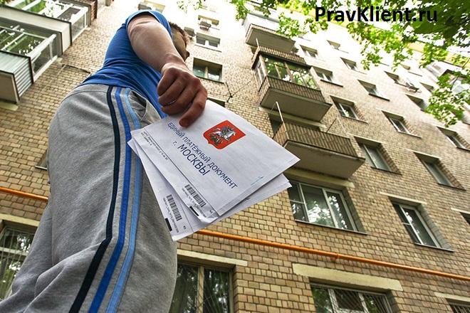 Мужчина держит в руке платежки ЖКХ на фоне дома