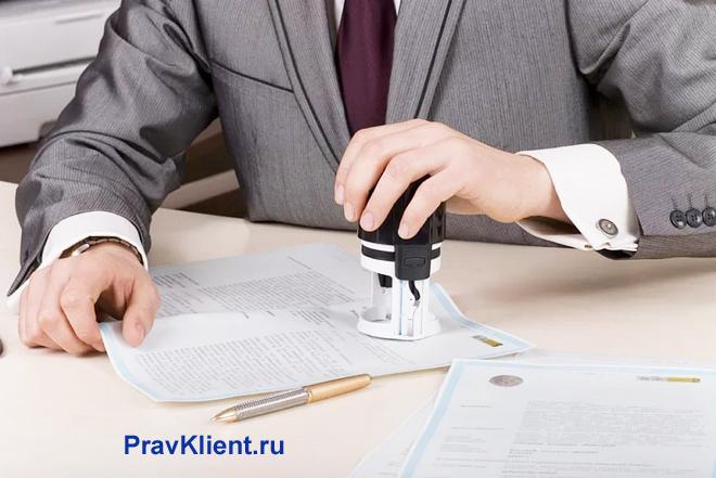 Бизнесмен ставит штамп на документах
