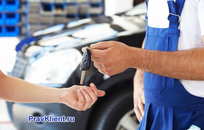 Сотрудник автосервиса отдает ключи от машины владельцу