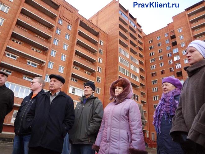 Жители стоят на фоне кирпичного дома
