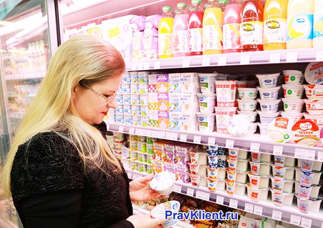 Девушка рядом с витриной кисло-молочной продукции