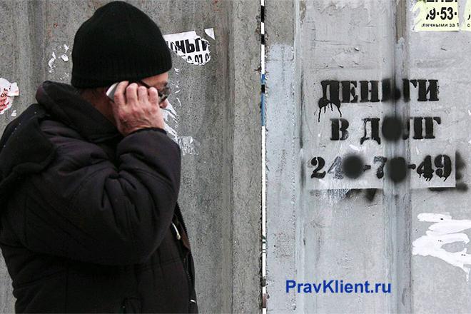 Мужчина звонит по телефону рядом с подъездом дома