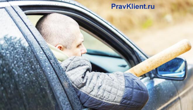 Водитель едет в машине с битой в руках