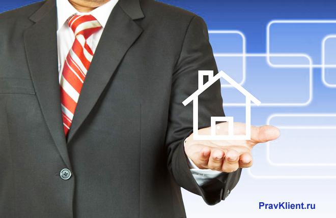 Бизнесмен держит на руке нарисованный домик