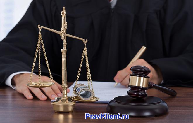 Судья пишет на листке бумаги, рядом стоят весы Фемиды, деревянный молоточек