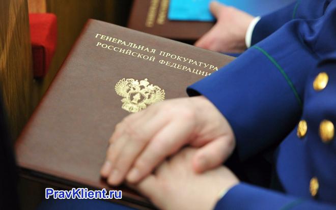 Прокурор держит в руке папку