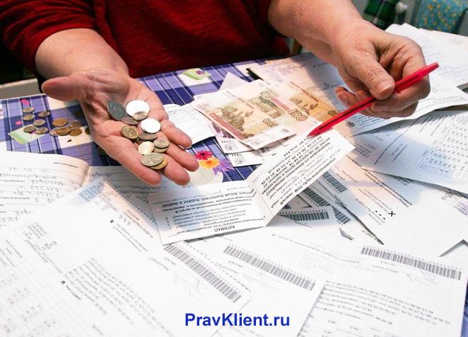 Женщина считает деньги за платежки ЖКХ