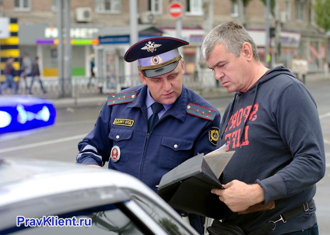 Сотрудник ГИБДД проверяет документы у водителя