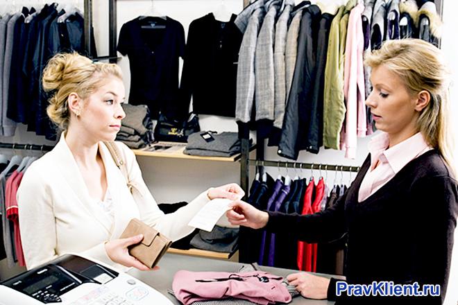 Девушка возвращает покупку в магазин одежды