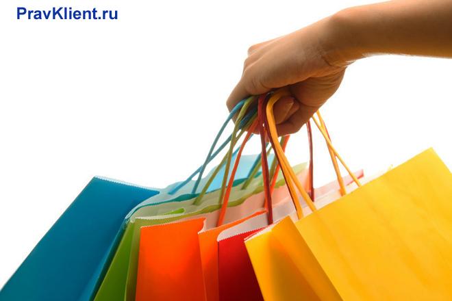 Девушка держит в руке пакеты с покупками
