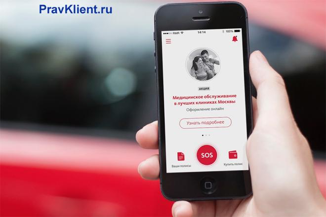 Человек держит в руке телефон с банковским приложением