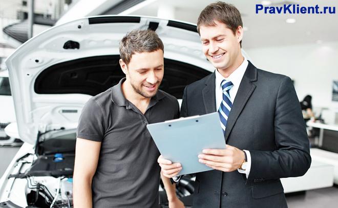Менеджер консультирует покупателя в автосалоне