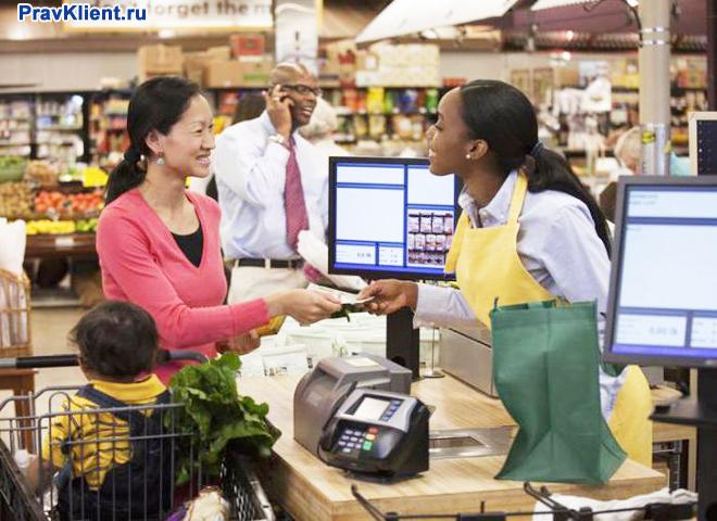 Женщина оплачивает купленные продукты на кассе