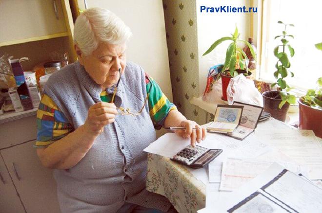 Пенсионерка за кухонным столом разбирается в платежных документах