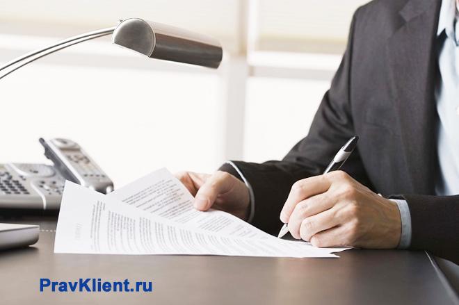 Мужчина за письменным столом подписывает документы