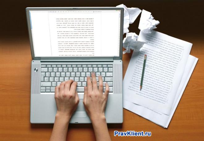 Девушка печатает документ на ноутбуке