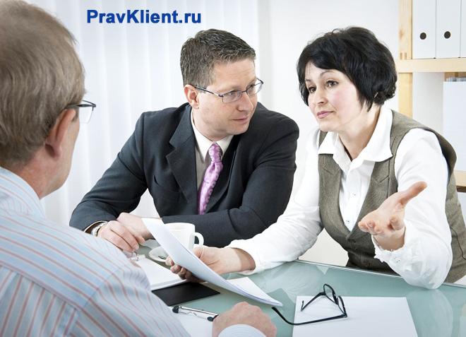 Женщина объясняет содержимое документов коллегам