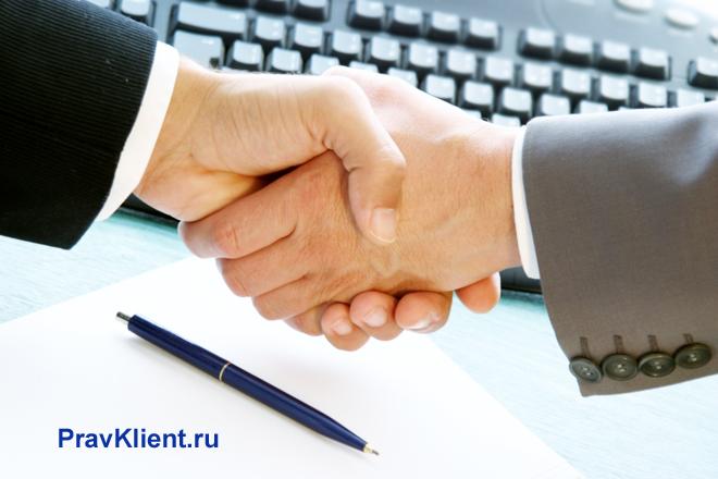 Мужчины жмут друг другу руки над компьютерным столом