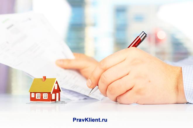 Мужчина подписывает документы на недвижимости
