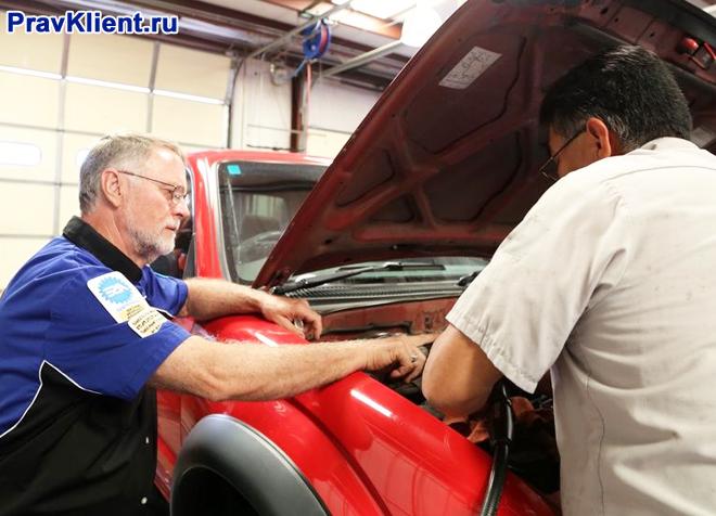 Двое мужчин осматривают автомобиль на неисправность