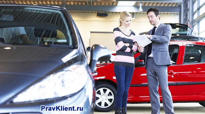 Менеджер выдает покупательнице автомобиля на руки документы