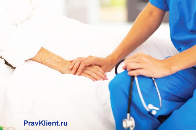 Врач держит за руку пациента на больничной койке
