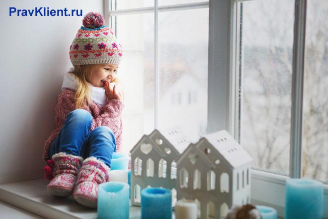 Маленькая девочка сидит на подоконнике и смотрит в окно, рядом стоит игрушечный домик