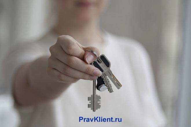 Девушка держит в руке связку ключей