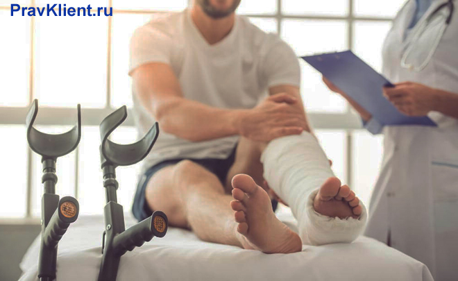 Врач осматривает мужчину со сломанной ногой