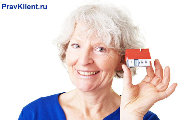 Пенсионерка держит в руке домик