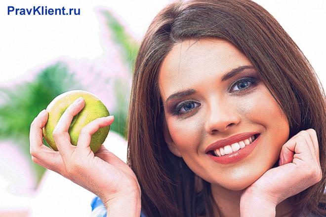 Девушка держит в руке зеленое яблоко