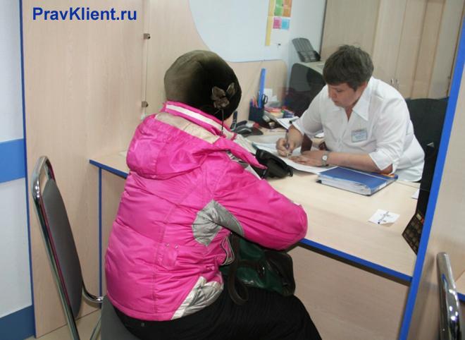 Женщина записывается на прием к врачу в регистратуре