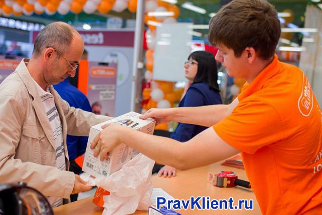 Продавец выдает покупку покупателю