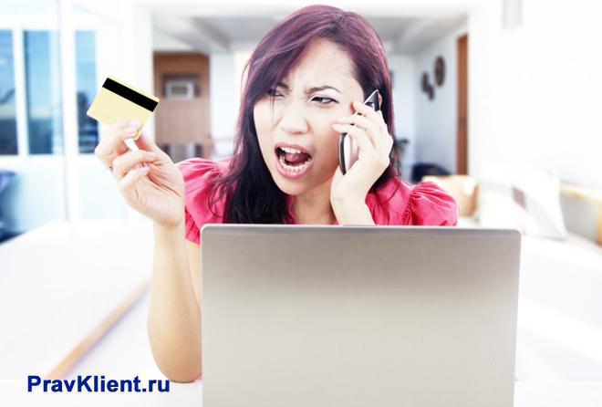 Девушка ругается по телефону и держит в руке банковскую карточку