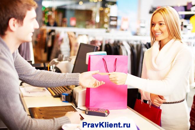 Девушка расплачивается безналичным расчетом за покупки в магазине одежды