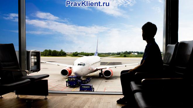 Мужчина смотрит на самолет из окна