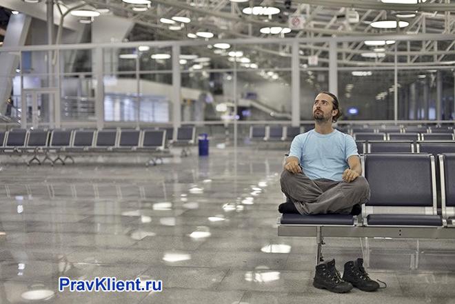 Мужчина сидит один в зале ожидания