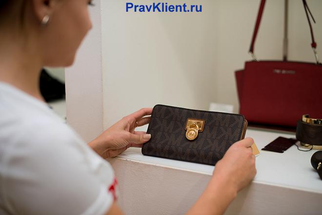 Девушка выбирает кошелек в магазине