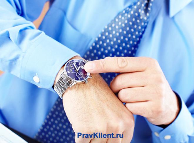 Мужчина смотрит время на наручных часах