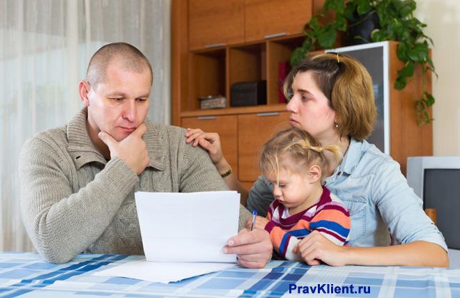 Семья с ребенком сидят вместе за столом