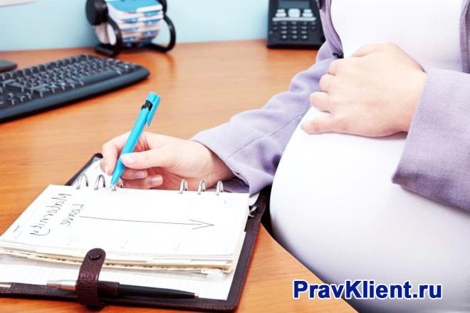 Беременная девушка делает записи в тетради