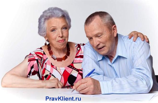 Мужчина пишет на листке бумаги, рядом с ним сидит его жена