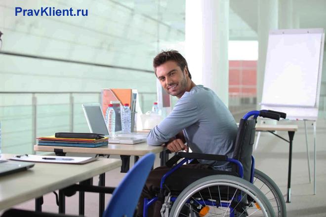 Мужчина в инвалидном кресле работает в офисе