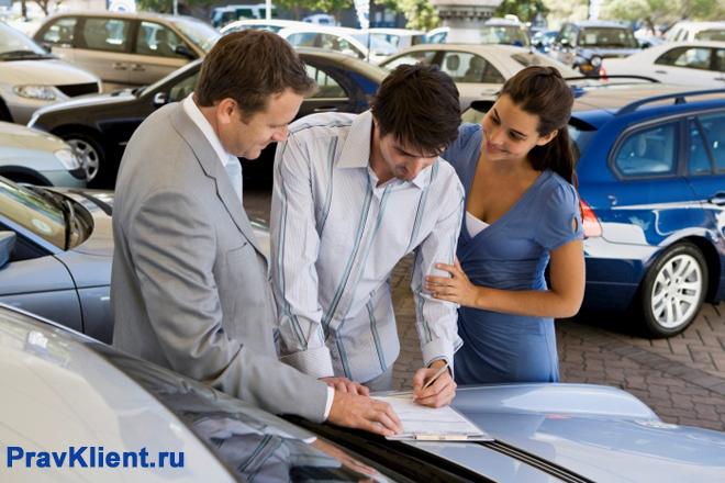 Мужчина подписывает документы на машину