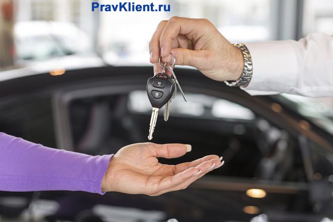 Продавец вручает ключи от автомобиля новому владельцу