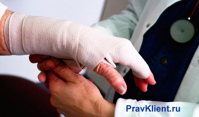 Врач бинтует руку пациенту