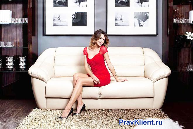 Девушка в красном платье сидит на белом диване