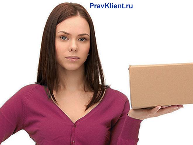 Девушка держит в руке картонную коробку