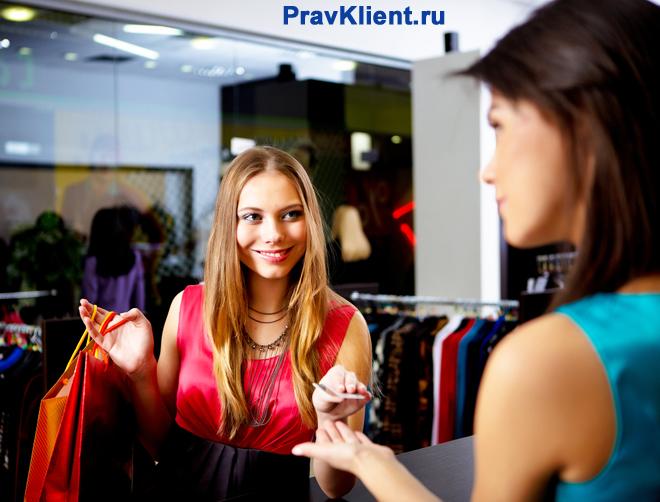 Девушка возвращает платье обратно в магазин